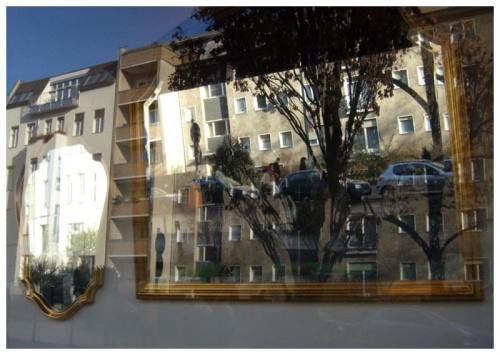 Zwei Spiegel und Schaufensterscheibe spiegeln Häuser